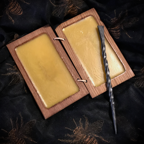 From Daegrad Tools: a Roman-style pair of wooden frames  filled with beeswax to serve as a writing tablet, laced together to form a book.  Also shown is an iron stylus.